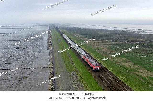 dpatop - A Deutsche Bahn train travelling along the Hindenburgdamm between Sylt and Niebuell, Germany, 17 May 2017. The dam turns 90 years old on 01 June 2017