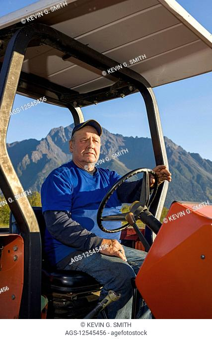 A farmer wearing a blue shirt sits on an old red tractor in an open field, Pioneer Peak in the background, South-central Alaska; Palmer, Alaska