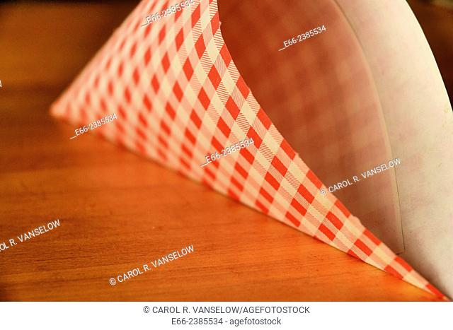 Red and white checkered paper french fries sack laying on wooden table