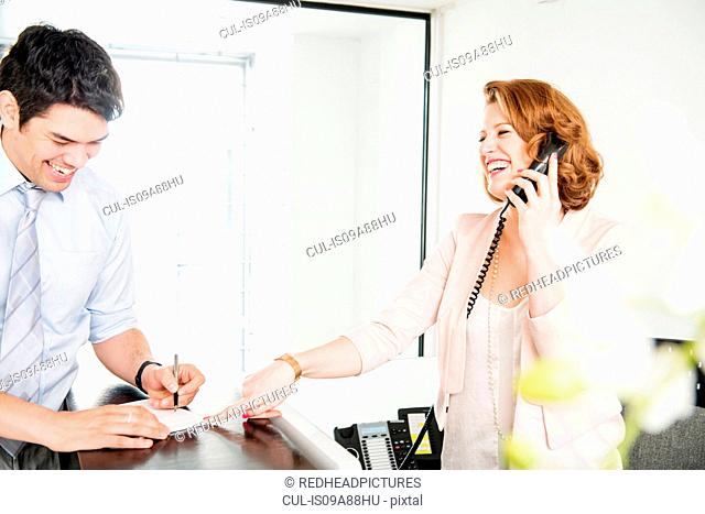 Man signing form at reception, woman on telephone