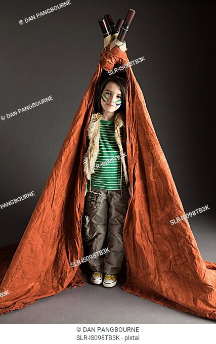 Young boy dressed up in Native American outfit, with teepee