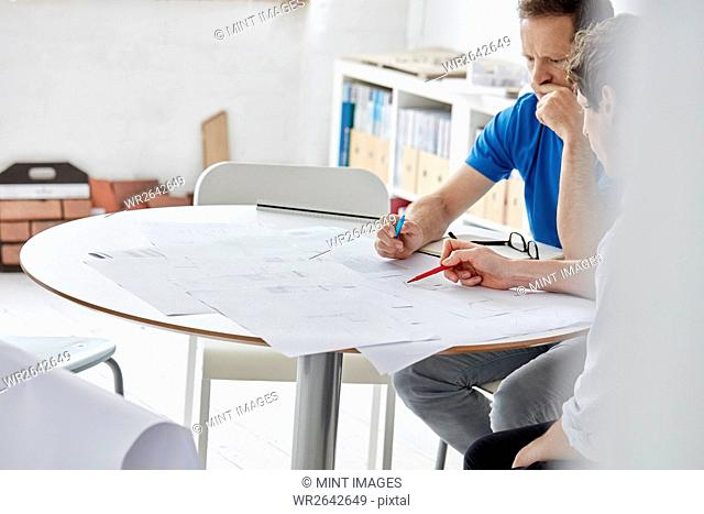 A modern office. Two people at a meeting discussing paper plans and using pens to draw and make amendments