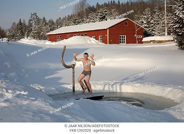 Young Happy Man by Ice Hole in Väike Trommi Tourism Farm, Valga County, Estonia