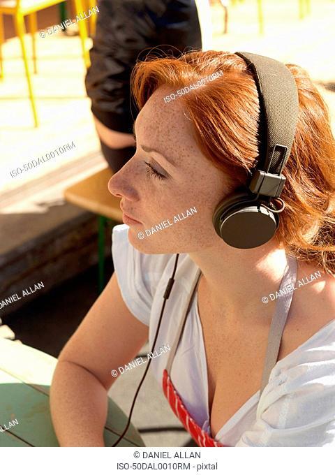 Woman in apron listening to headphones