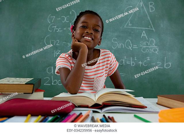 Schoolgirl reading book in classroom