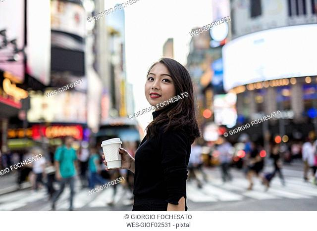 USA, New York City, Manhattan, young woman with coffee to go on the street