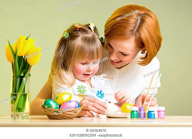 mother and kid girl painting easter eggs together