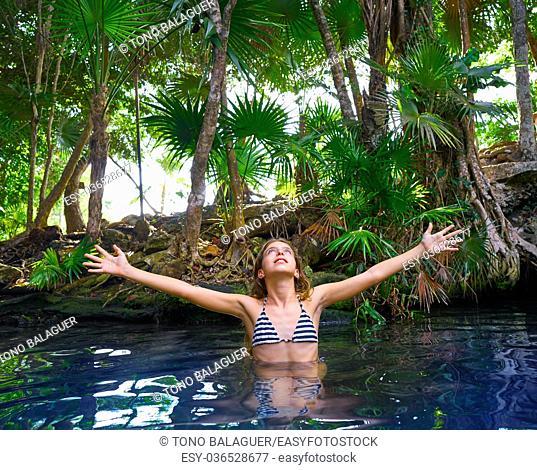 Girl bath in Cenote sinkhole at Riviera Maya of Mayan Mexico