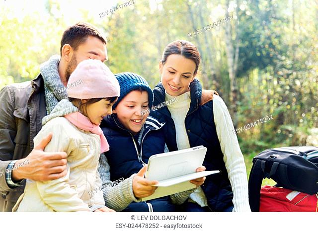 camping, travel, tourism, hike and people concept - happy family with tablet pc computer and backpacks at camp in woods