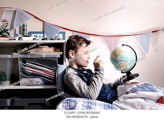 Boy sitting up in bed pointing at globe