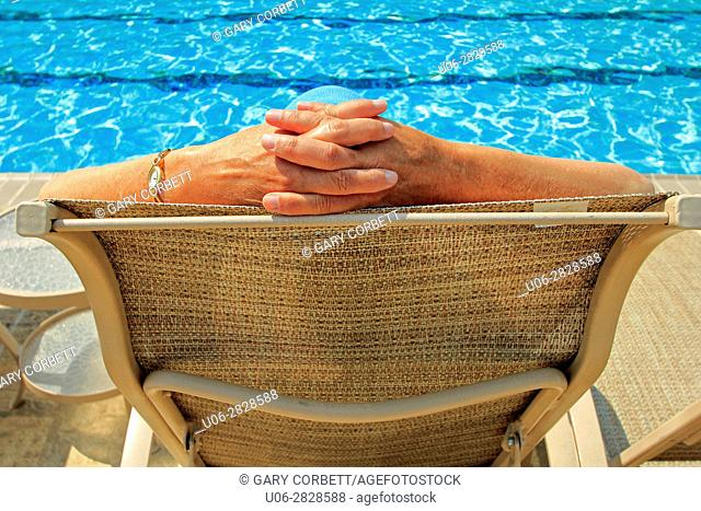 A senior woman in a chair beside a pool