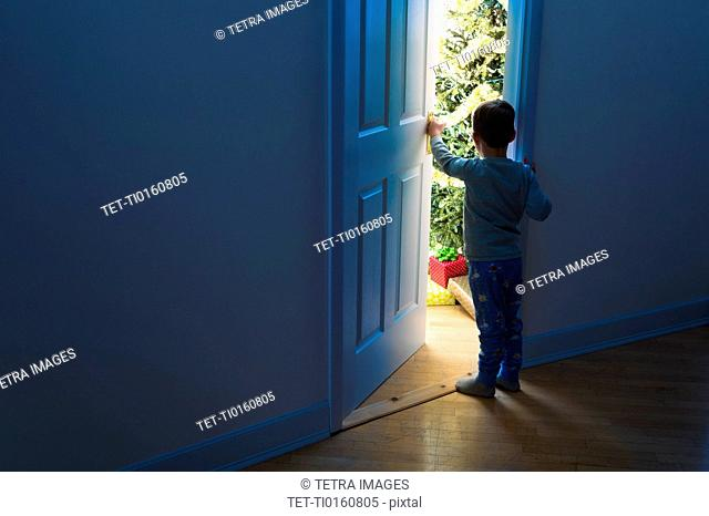 Boy (4-5) peeking through doorway