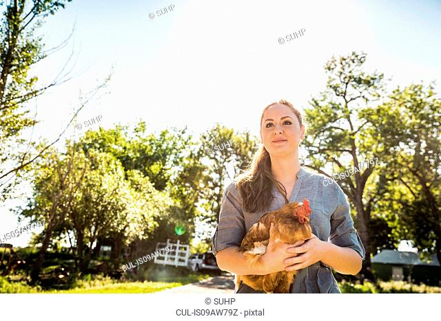 Woman holding chicken looking away smiling