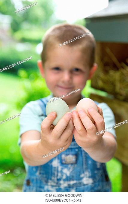 Boy holding hens eggs looking at camera smiling