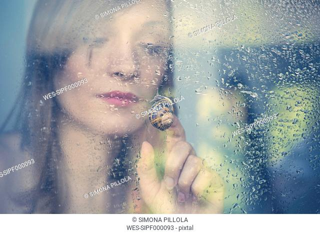 Woman watching snail creeping at outside of the windowpane