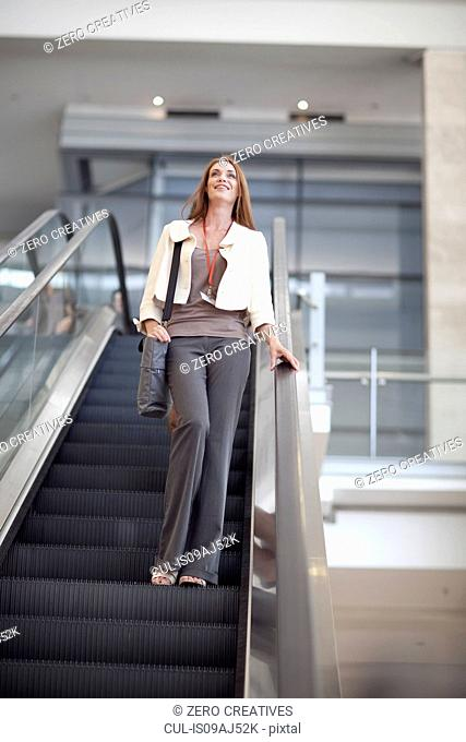 Businesswoman moving down on conference centre elevator