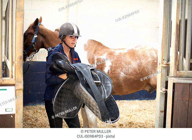 Young woman removing saddle from horse