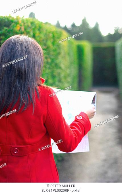 Lady looking at map in a maze