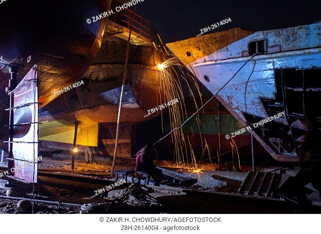 DHAKA, BANGLADESH - FEBRUARY 18 : A worker use welder to make repairs a large ferry at dockyard on the river bank of Buriganga in in Dhaka
