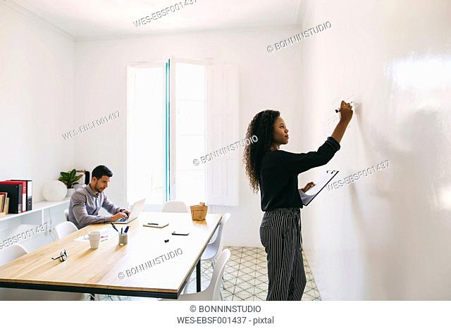 Young businesswoman preparing meeting, writing on wall, colleague working in backgound