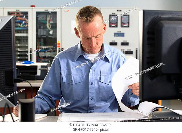 Electrical engineer reviewing logs in central operations room of power plant