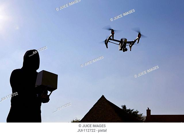 Man operating surveillance drone in blue sky