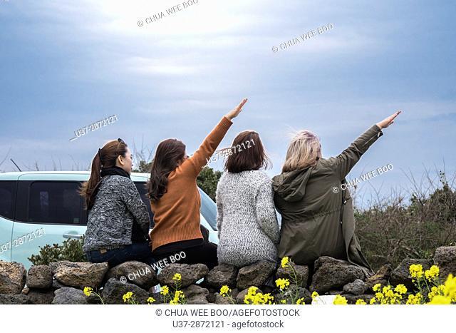Happy girls taking photo with handphone at Jeju Gimnyeong Seongsegi beach, Korea