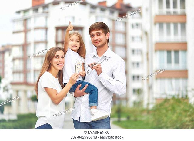 Cute little girl smiling showing thumbs up her parents holding keys to their new home in apartment building on the background