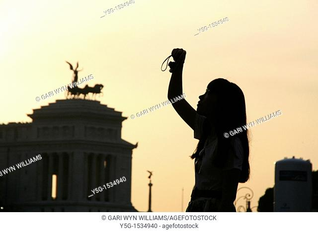 woman taking photograph on via dei fori imperiali street in rome italy