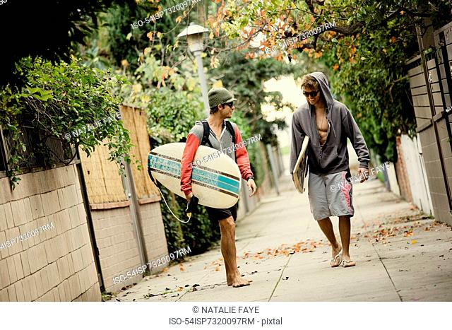 Men carrying surfboards on city street