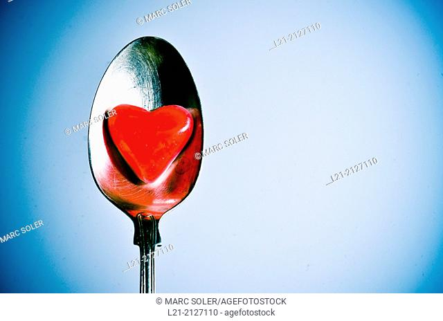 Red heart in a metal spoon