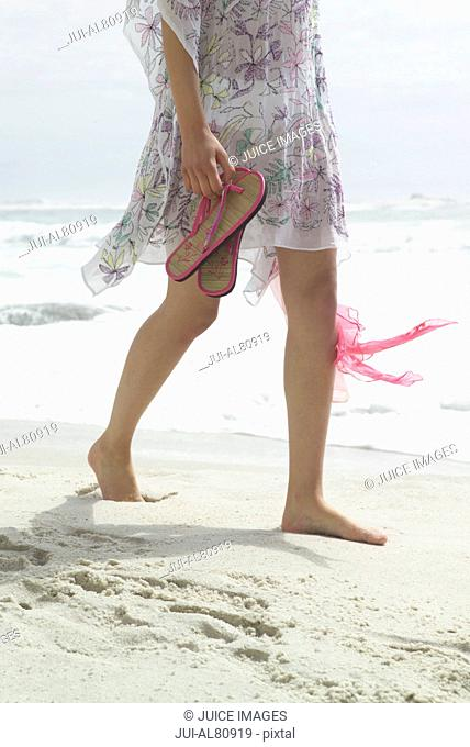 Woman holding sandals and walking on beach