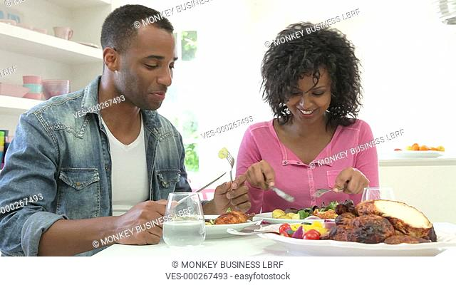 Young African American couple sitting at table enjoying meal together.Shot on Canon 5d Mk2 with a frame rate of 25fps