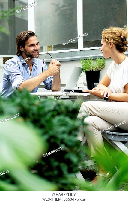Happy couple working from home, sitting in their garden