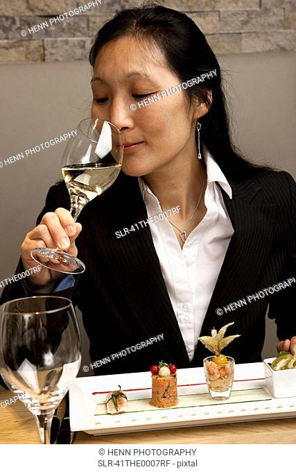 Businesswoman examining wine at table