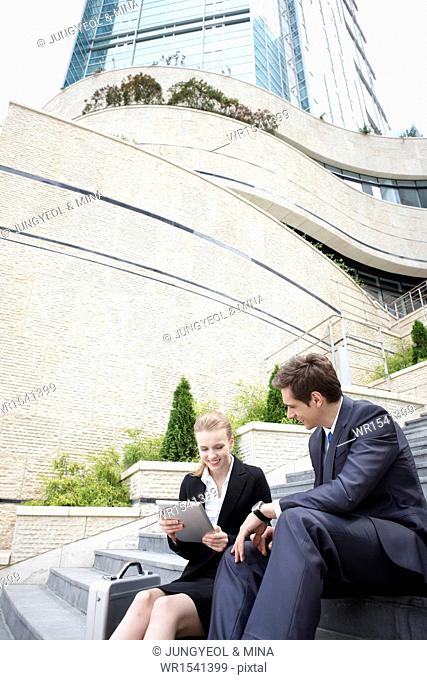 two business people sitting on the stairs together