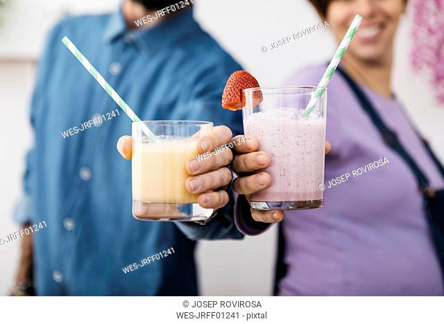 Couple with glasses of different smoothies ready to drink, partial view