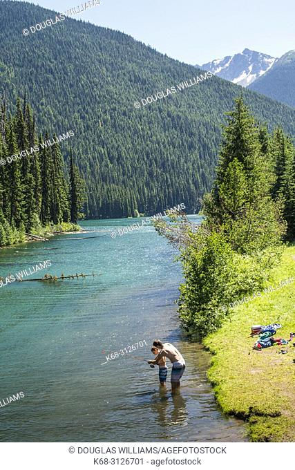 A father helps his son fish on Lightning Lake in E. C. Manning Provincial Park, British Columbia, Canada