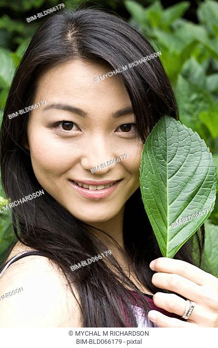 Smiling Japanese woman holding leaf
