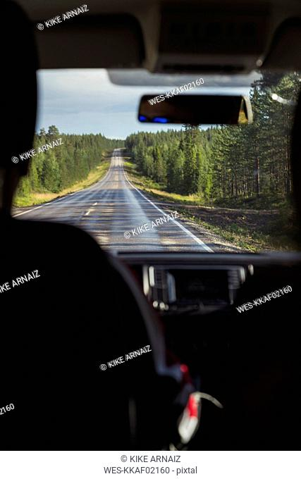 Finland, Lapland, interior view of man driving car in rural landscape