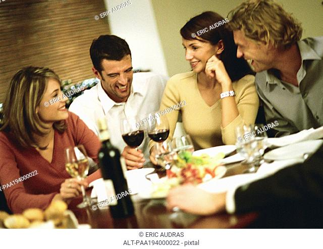 Group of young people around table, drinking wine and laughing