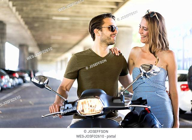 Couple with motor scooter smiling at each other at underpass