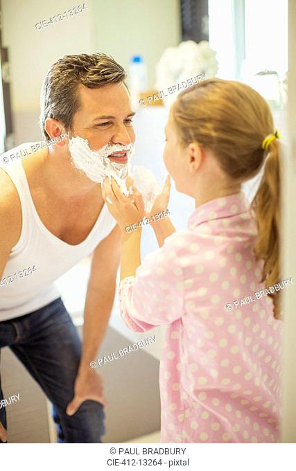 Girl rubbing shaving cream on father's face