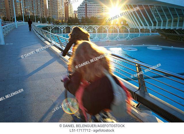 girls cycling over a bridge, Ciudad e las Artes y las Ciencias, Valencia, Spain
