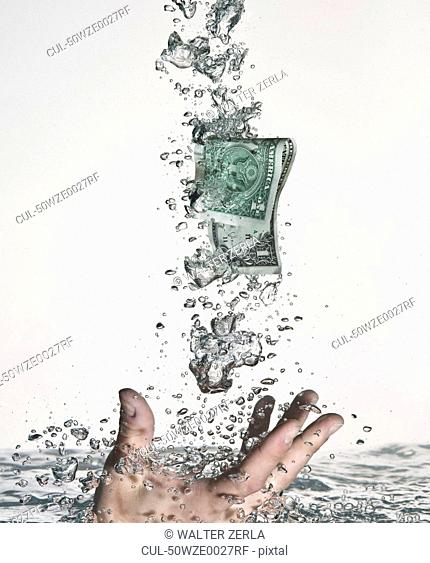 Hand grasping dollar bill in water
