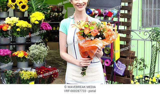 Female florist holding a bouquet of flowers in flower shop