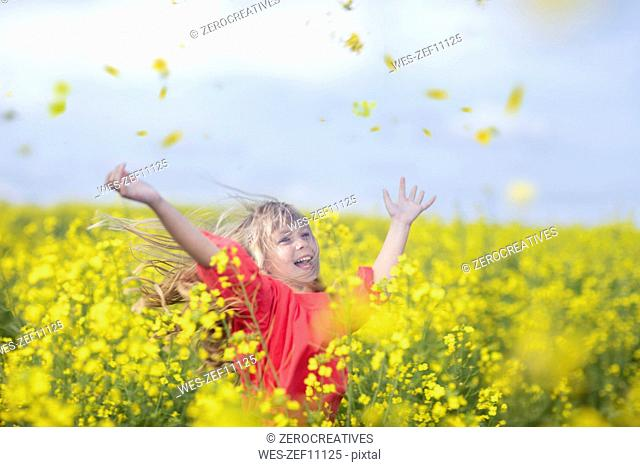 Happy little girl standing in rape field throwing blossoms in the air