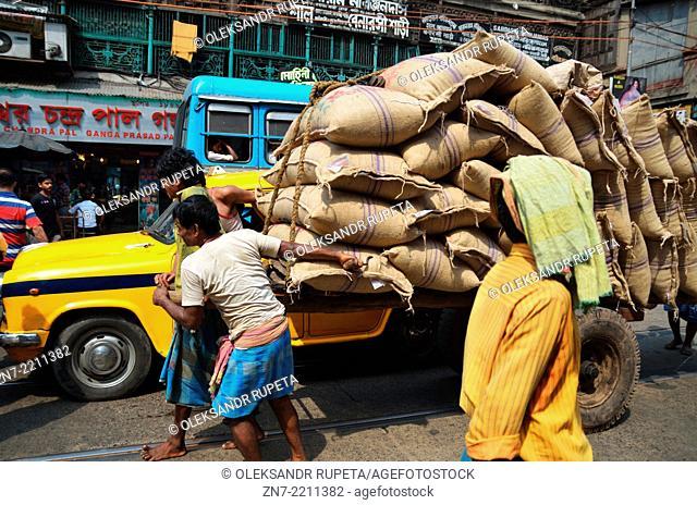 Men carry giant sacks through the traffic, Kolkata, India