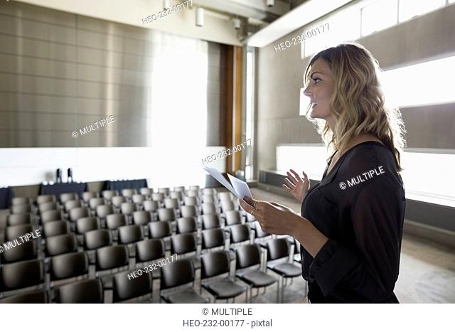 Woman reviewing notes on stage in empty auditorium
