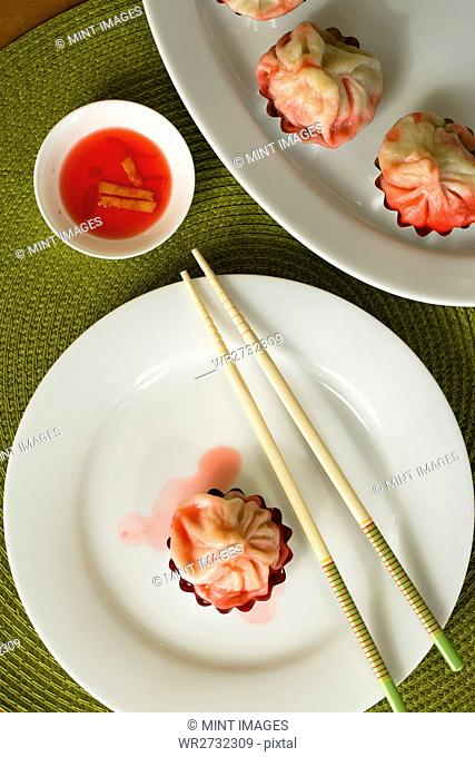 Dim sum arranged on plates with a pair of chopsticks, with a small dish of sauce, overhead view